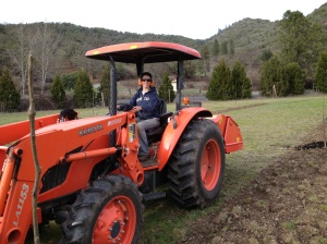Anna is slowly learning to operate the tractor.